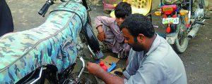 バイクの修理工として働く少年